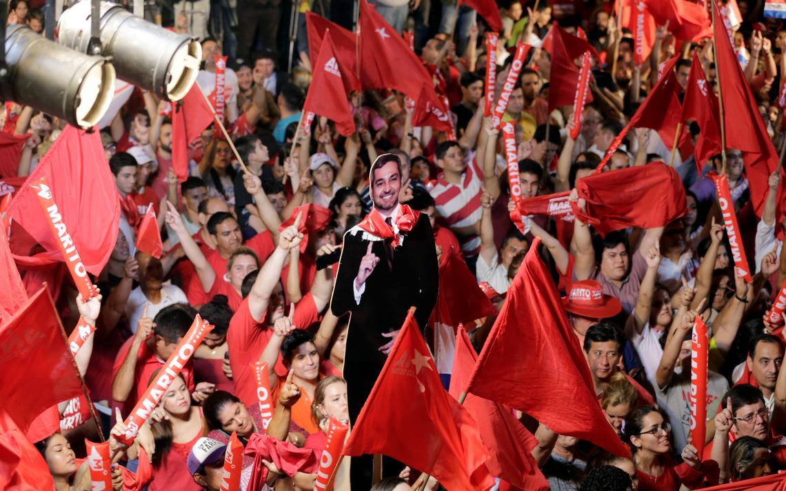 Dezenas de pessoas vestindo vermelho ou erguendo bandeiras vermelhas. Imagem de papelão do presidente eleito é erguida.