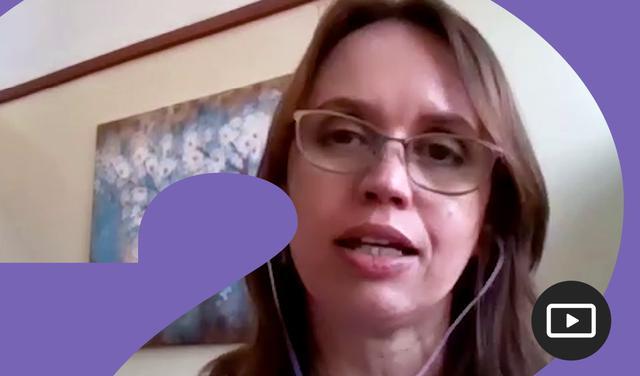 Captura do vídeo da professora médico Patrícia Jaime, que aparece em frente a um quadro decorativo com flores e a uma parede branca usando fones de ouvido e óculos de grau.