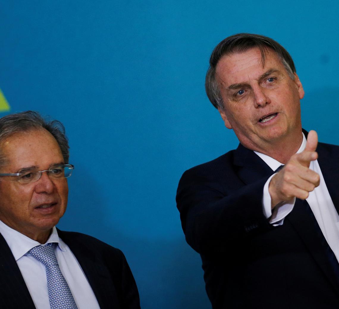 Guedes e Bolsonaro estão sentados lado a lado. Com a mão direita, Bolsonaro aponta para a frente e fala alguma coisa. Guedes olha na direção que o presidente aponta.