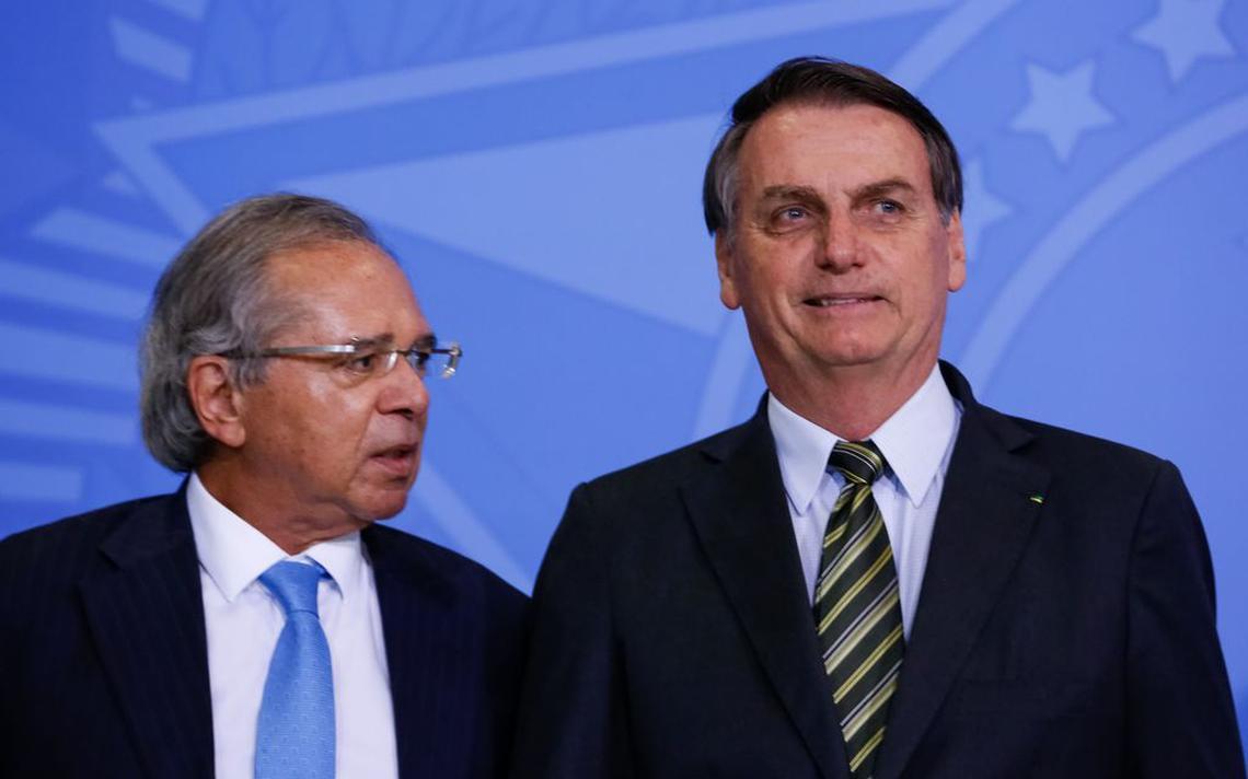 O presidente Jair Bolsonaro e o ministro da Economia, Paulo Guedes, no evento de lançamento do Programa Verde Amarelo, em Brasília. Guedes está à esquerda de Bolsonaro, e olha em direção ao presidente. Já Bolsonaro sorri e olha para trás da câmara. Ao fundo, um painel azul.