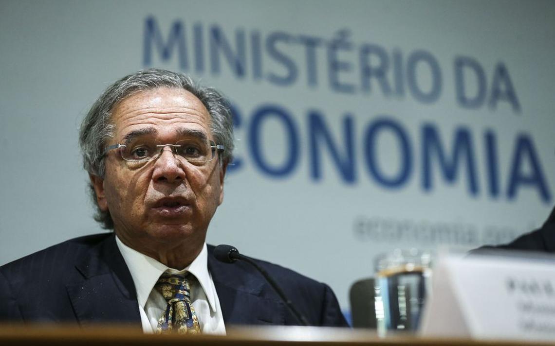 O ministro Paulo Guedes aparece atrás de uma mesa, do ombro para cima. Ele veste um terno e gravata, e olha em direção à câmera, como quem está no meio de uma fala.