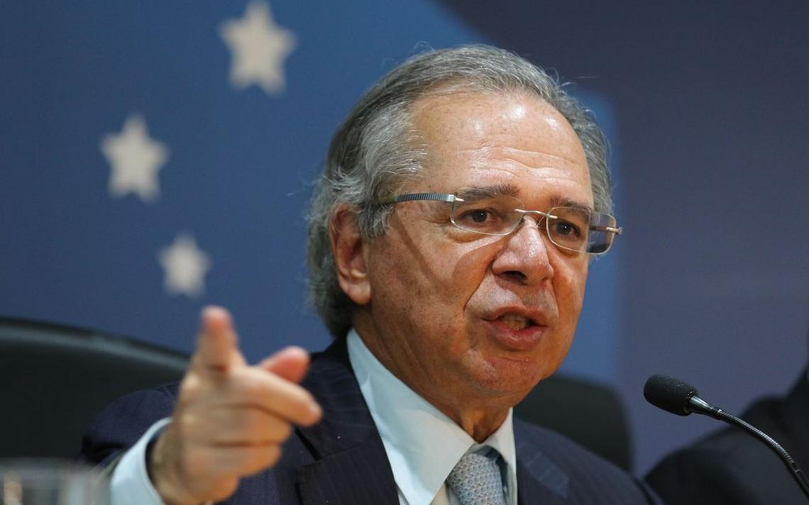 O ministro Paulo Guedes na coletiva de anúncio do Plano Mais Brasil. Ele veste um terno e gravata e está falando, gesticulando com o braço direito. Ele aponta o indicador direito para o lado, como quem está explicando algo.