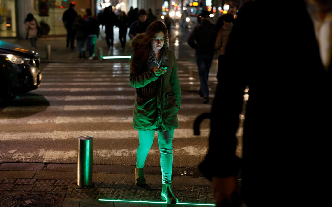 Pedestre usa smartphone ao atravessar rua em Tel Aviv, em março de 2019