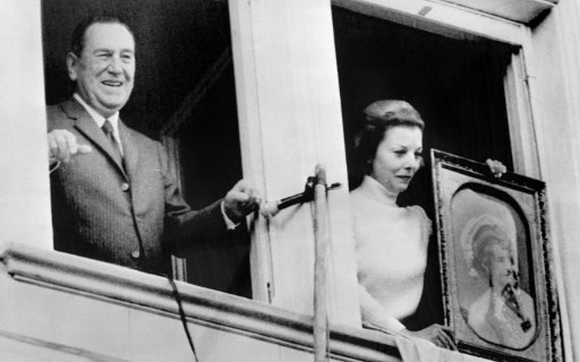 Nas janelas de uma casa, Perón olha para o público. Isabel Perón mostra ao público um retrato de Evita Perón.