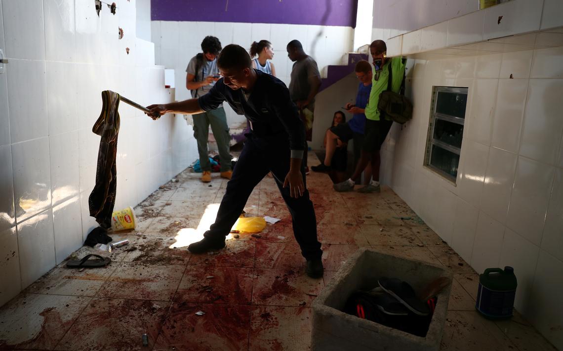 Perito analisa um tecido deixado no chão ensanguentado de uma casa onde foram encontrados 9 corpos, após ação policial no morro do Fallet, no Rio