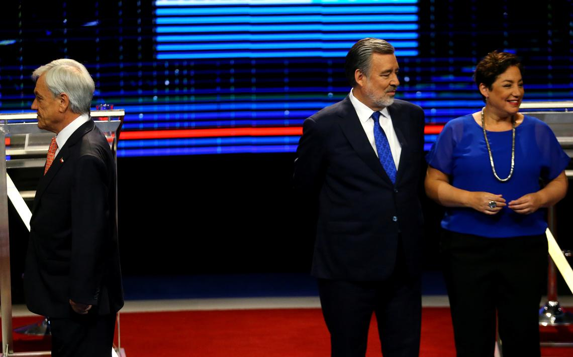Piñera aparece no canto, sozinho e de costas para os candidatos rivais Guillier e Sánchez, que estão lado a lado.