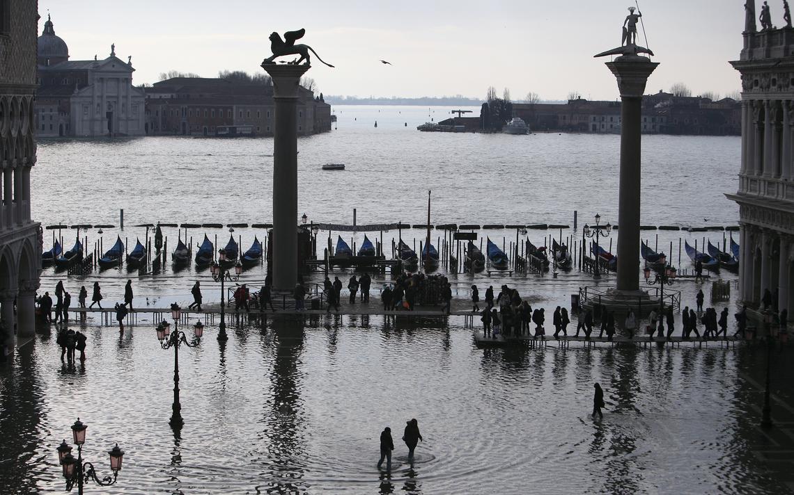 Pessoas caminham na Piazza San Marco, em Veneza, durante época de cheias