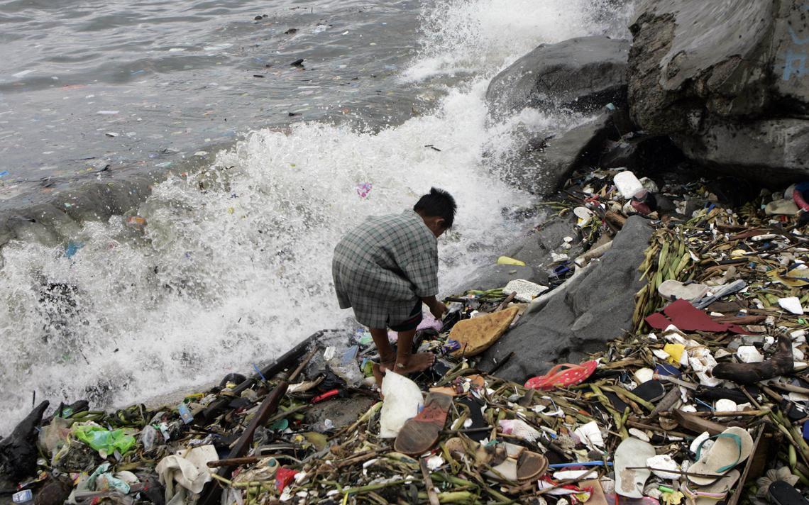 Garoto recolhe plástico que se acumulou na costa das Filipinas após passagem de tufão, em 2007