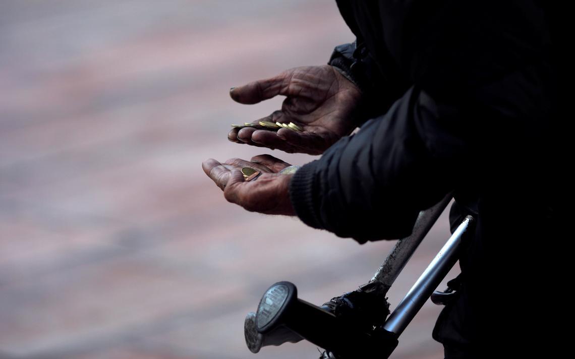 Um mendigo conta moedas em Málaga, na Espanha