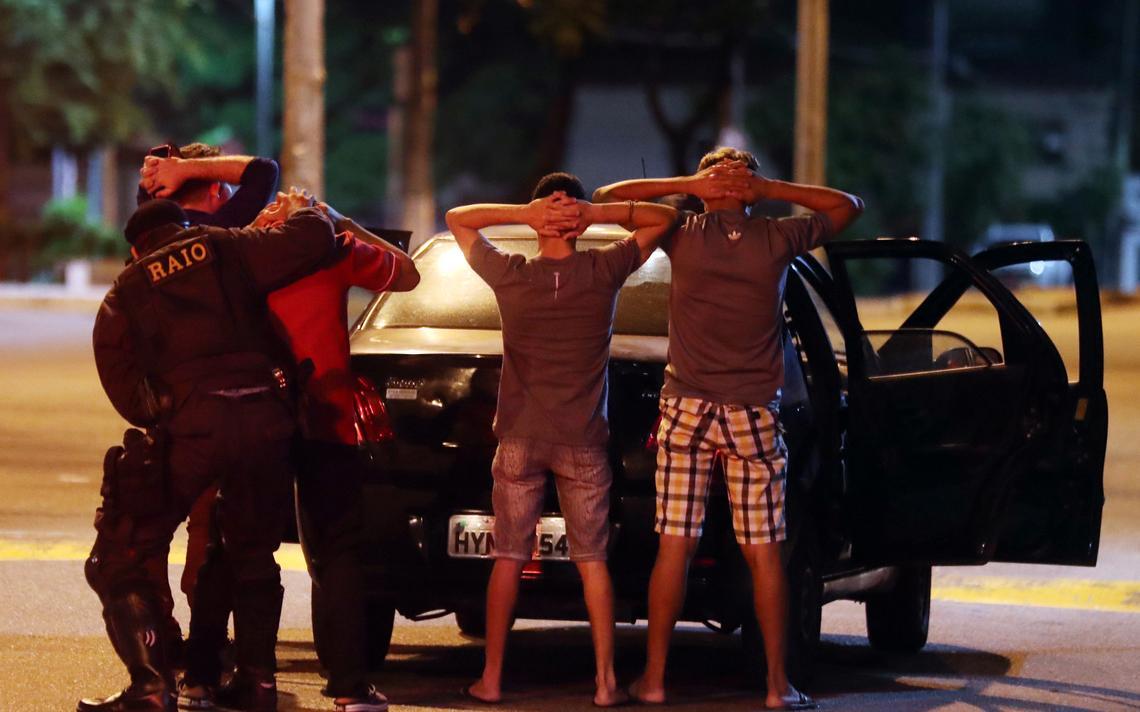 Atrás do carro parado e com as portas abertas, quatro homens estão em pé e com as mãos na cabeça. Um policial militar revista os quatro.