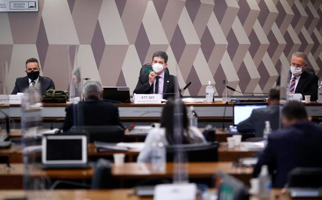 Foto tirada ao fundo mostra várias cadeiras e, no final, a mesa principal da sala da CPI, com Elcio Franco Filho, Randolfe Rodrigues e Renan Calheiros sentados, de máscara, com placas de vidro entre eles