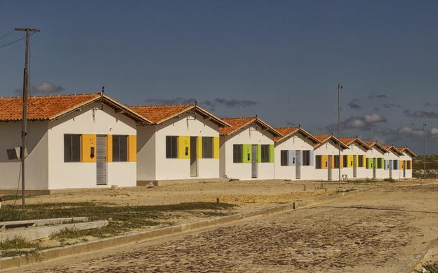 Fila de casas térreas, brancas, com uma porta, duas janelas e telhado triangular, todas idênticas. Elas estão em uma rua sem asfalto.