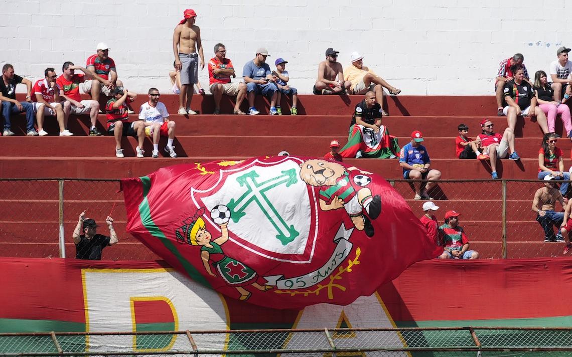 Alguns poucos torcedores na arquibancada do Canindé. Na grade, há uma bandeira comemorativa de 95 anos da Portuguesa com o escudo do clube.
