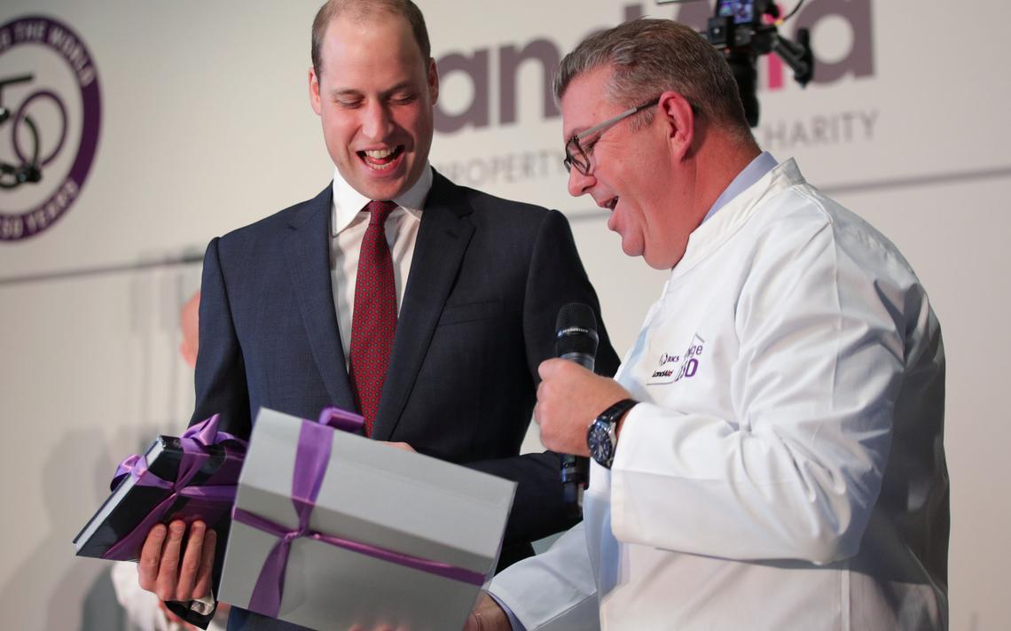 Prícipe William, da Grã Bretanha, recebe roupinhas de chef para seus filhos, Charlotte e George, em evento em novembro de 2017