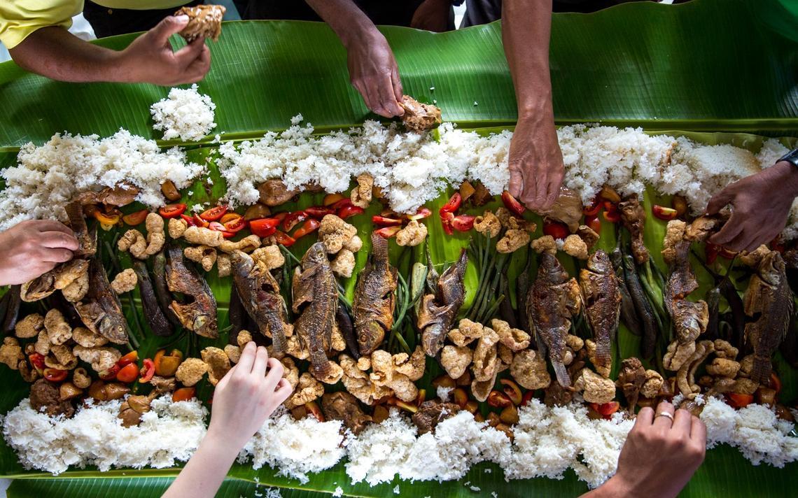 Locais e turistas partilham refeição nas Filipinas