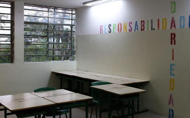 """Foto de canto de uma sala de aula vazia. Encostadas em uma das perdes estão algumas carteira escolares. Outras estão agrupadas no canto da imagem. Em uma das paredes lê-se em letras coloridas as palavras """"Responsabilidade"""", escrita na horizontal e, conectada a ela pela letra A, na vertical, a palavra """"solidariedade"""", que ocupa também parte do teto e do chão."""