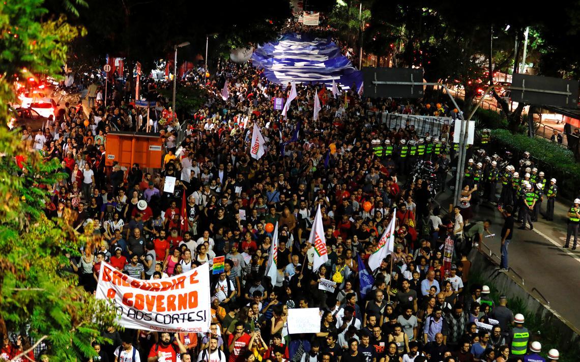 Multidão vista de cima, com bandeiras, faixas e cartazes. É possível ler uma faixa com os dizeres
