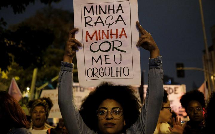Em primeiro plano, mulher segura cartaz com os dizeres 'minha raça, minha cor, meu orgulho'. Outras mulheres negras ao lado, em protesto na rua, à noite.