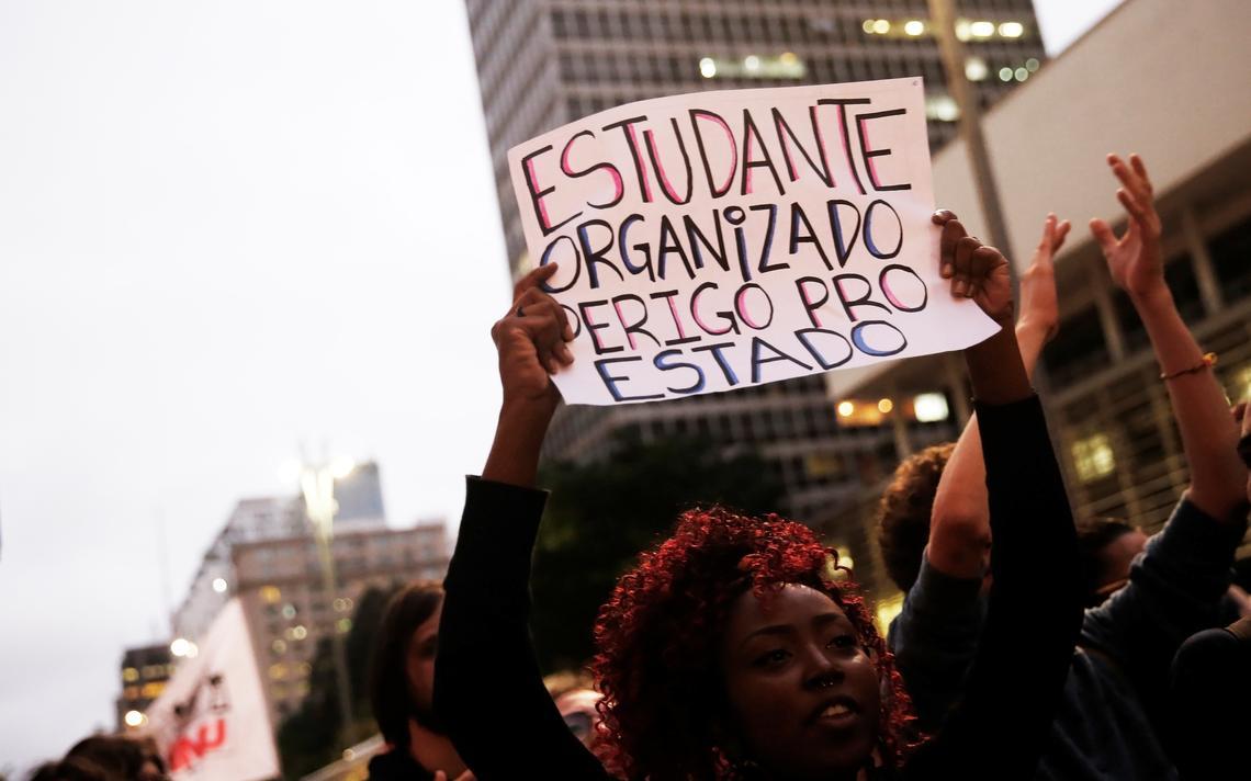 Em protesto, estudante mulher segura cartaz com os dizeres