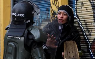 Policial da tropa de choque com escudo e capacete encurrala manifestante, que estende o braço para afastá-lo