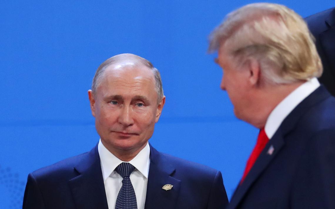 De frente, Putin está de pé com semblante fechado. Trump passa andando e é visto de lado.