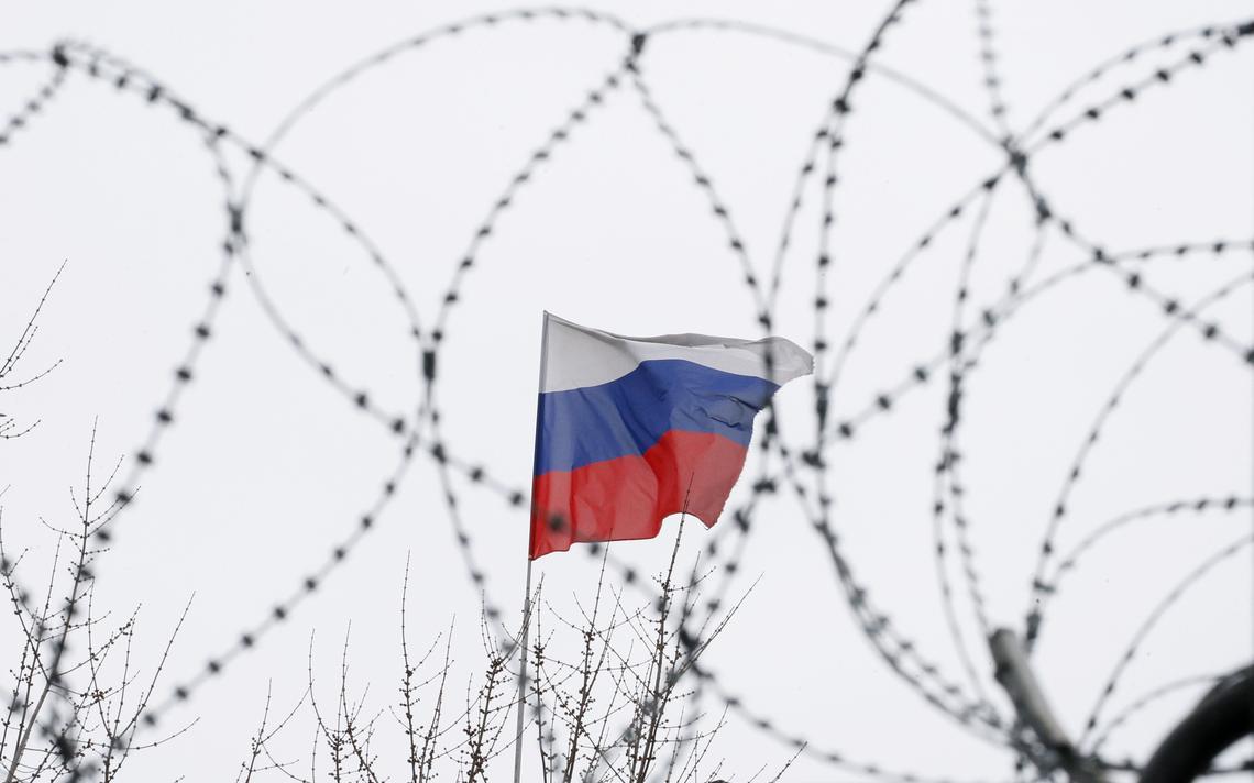 Bandeira russa vista atrás de arame farpado.