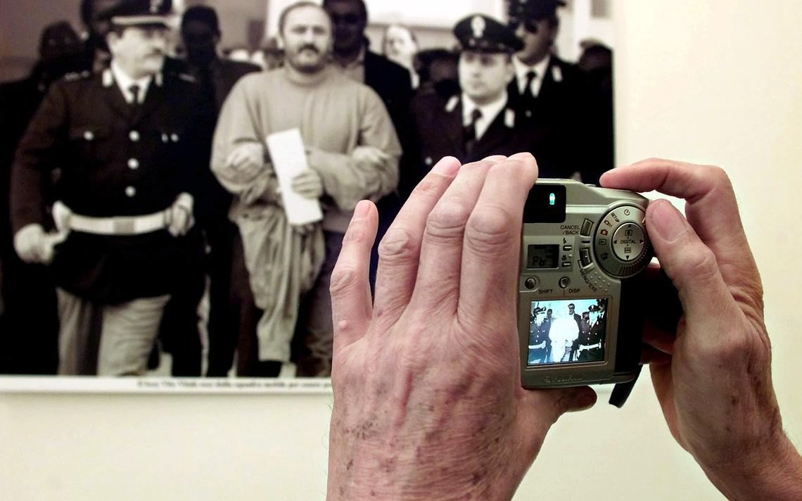 Visitante fotografa reprodução de imagem de ex-chefe da Máfia, Vito Vitale, sendo preso em 1998