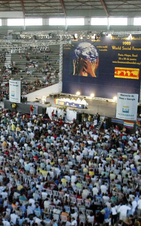 Mesa de debates em ginásio na edição 2003 do fórum