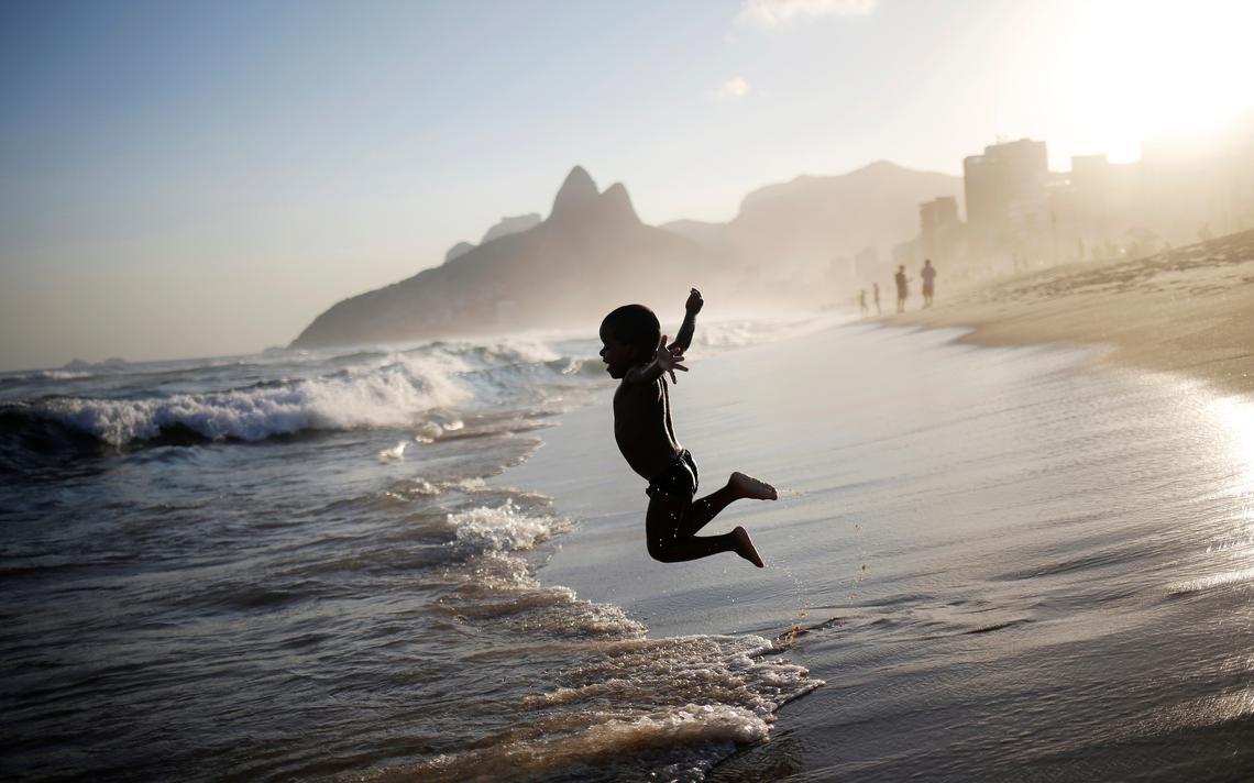 Criança brinca na praia de Ipanema, no Rio