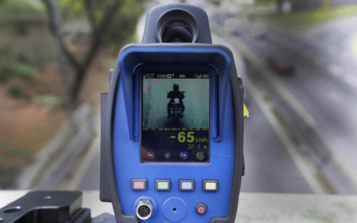 O visor de um radar móvel mostra moto e indica que o veículo está andando a 65 quilômetros por hora.