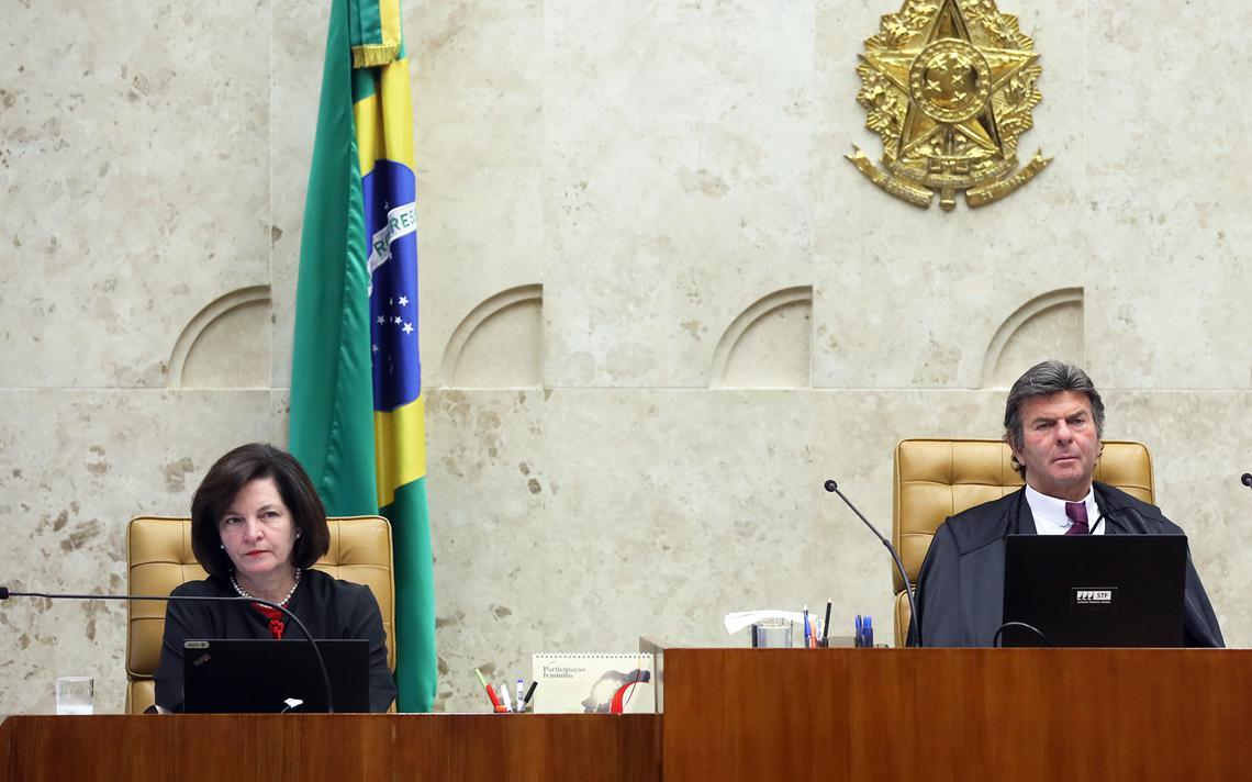 Sentada em seu lugar no plenário do Supremo Tribunal Federal, Raquel Dodge observa sessão. Atrás, uma bandeira do Brasil.