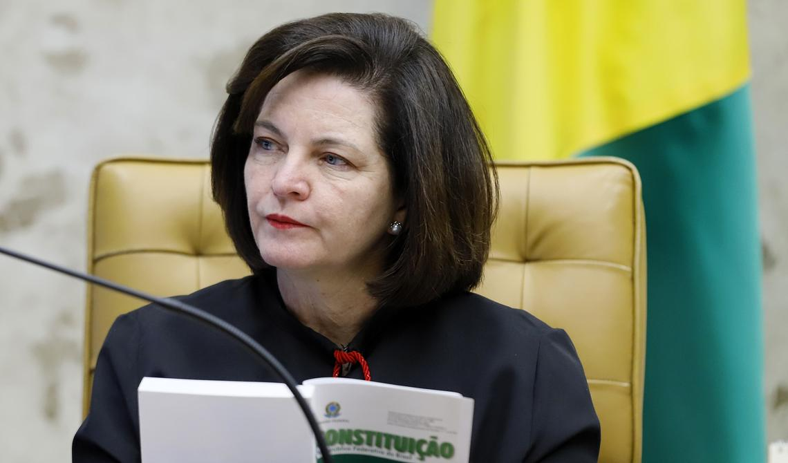 Sentada, Raquel Dodge observa discussões na sessão do plenário do Supremo. Ela está segurando um exemplar da Constituição Federal. O livro está aberto. Atrás, uma bandeira do Brasil.