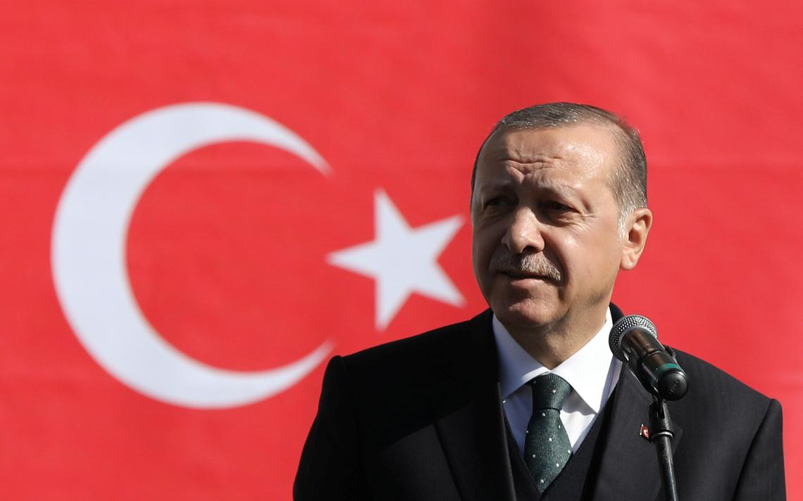 Erdogan em frente a um microfone. Atrás, a bandeira da Turquia.