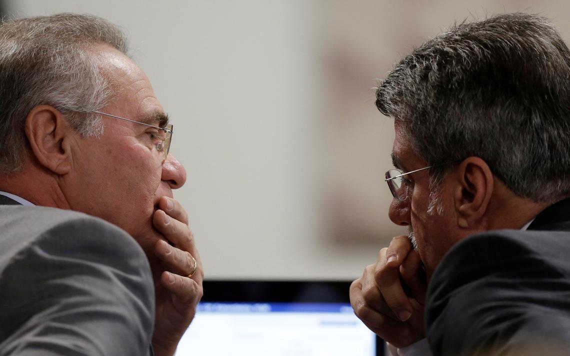 Com semblante reflexivo, senadores conversam lado a lado.
