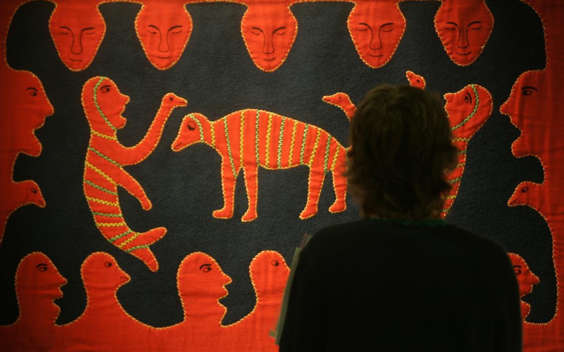 Mulher visita exposição com arte inuíte em Riga, em 2007