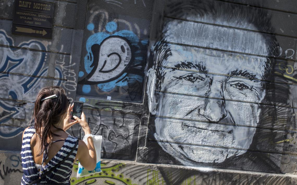 Mulher tira foto de pintura com rosto de Williams em Belgrado, na Sérvia, em 2014