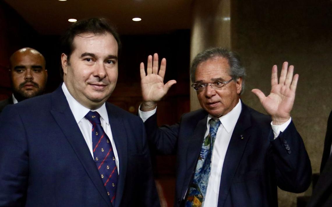 Maia ao lado de Guedes. O ministro está com os dois braços erguidos, com as mãos abertas.