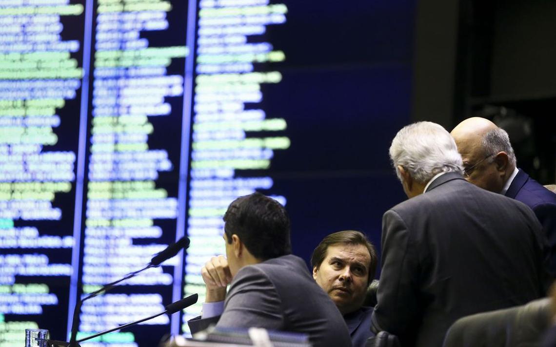Sentado à mesa diretora, Rodrigo Maia conversa com outros três deputados. Atrás deles, o painel de votação da Câmara.