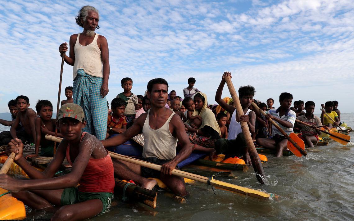 Dezenas de refugiados, inclusive crianças, remando em botes precários num rio.