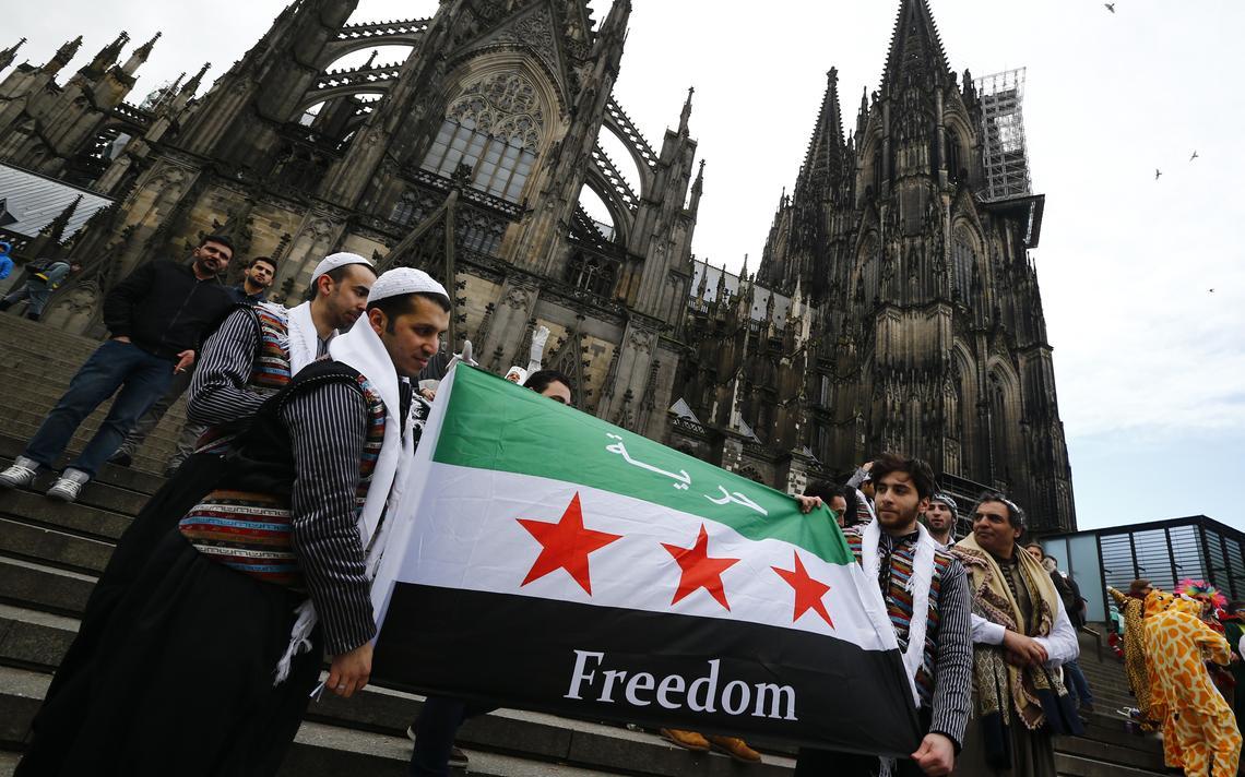 Nas escadarias da catedral, dois homens seguram uma variante da bandeira da Síria, com a palavra
