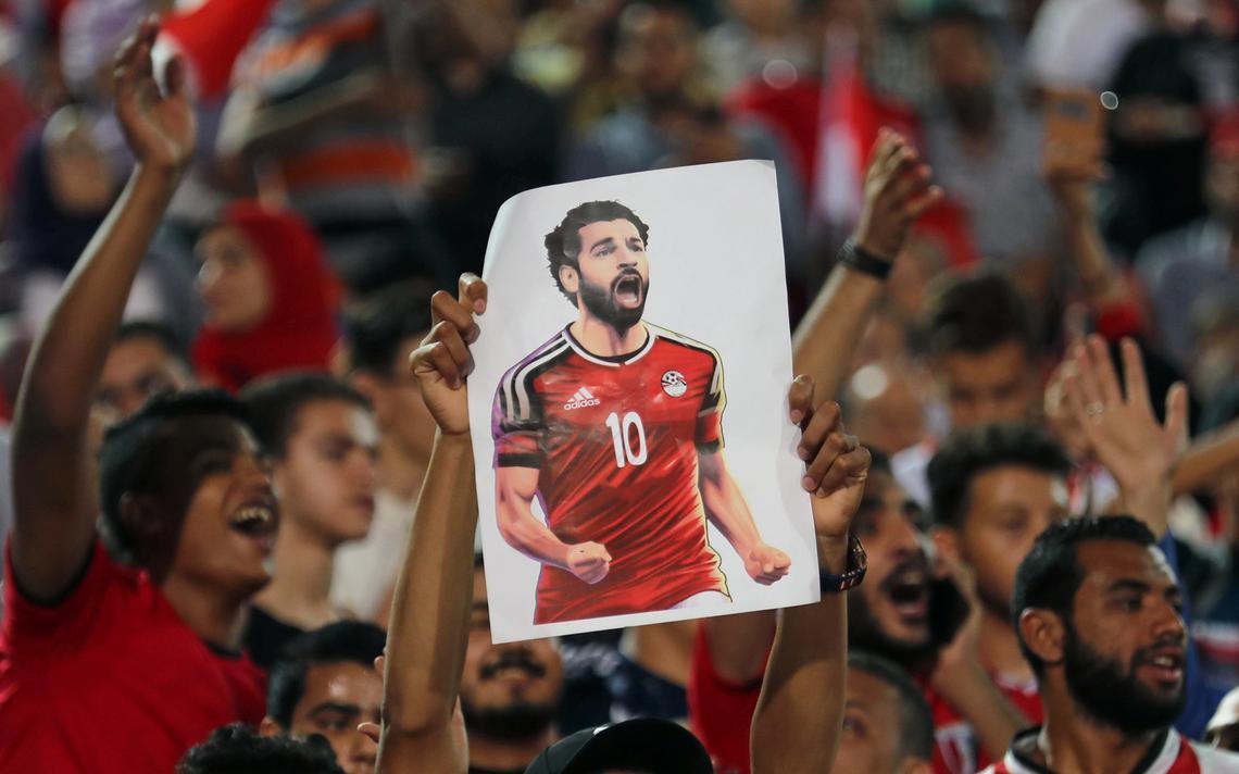 Torcedores sorridentes vibrando na arquibancada. Um deles segura um cartaz com a foto de Salah.