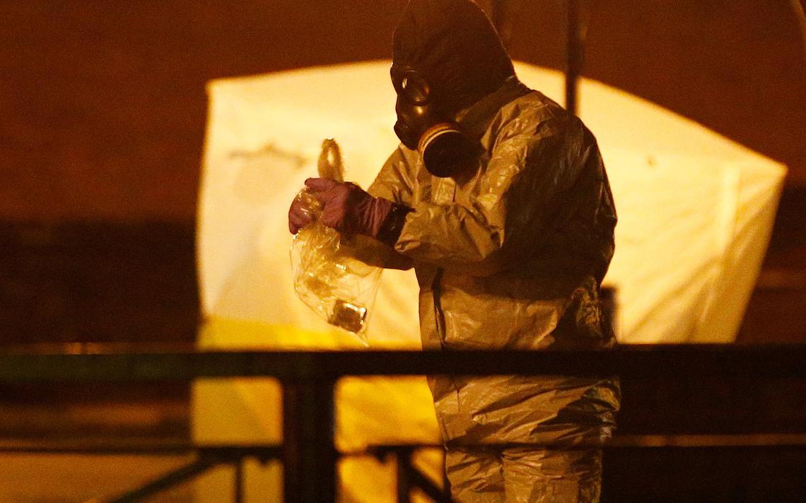Funcionário com vestes especiais e máscara de gás recolhe uma amostra dentro de saco plástico, à noite, em perímetro fechado.