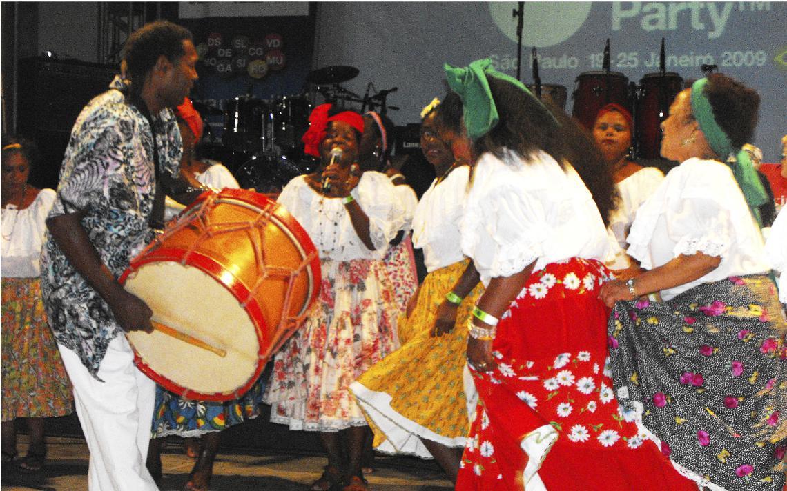 Pessoas tocam e dançam samba de bumbo