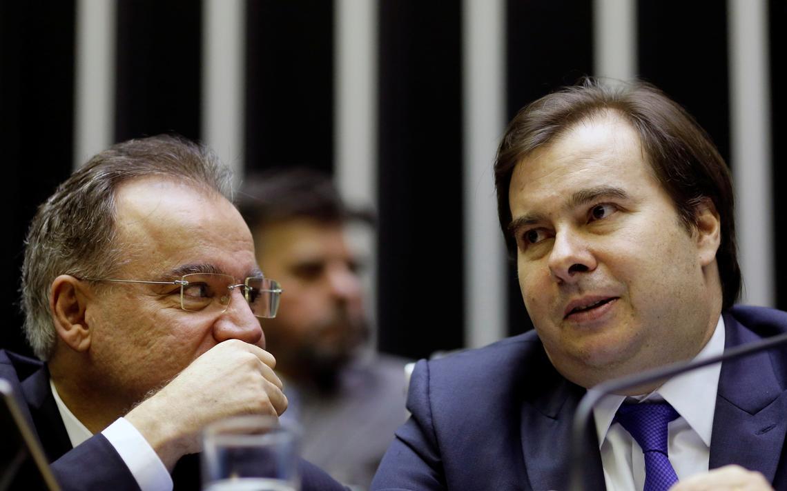 Sentados lado a lado em mesa do plenário da Câmara, Samuel Moreira e Rodrigo Maia conversam durante sessão.