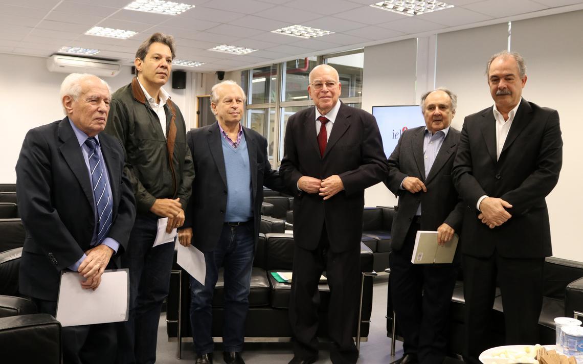 Lado a lado, os seis ex-ministros estão de pé e se preparam para foto, em poses formais. Eles estão dentro de uma sala na universidade. Alguns deles seguram pastas e papéis.