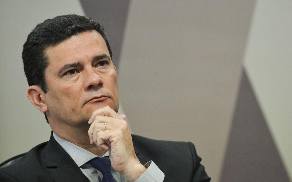 Sentado à mesa, Moro apoia a cabeça na mão direita. Ele está com semblante sério e observa senadores que o questionam na CCJ do Senado.