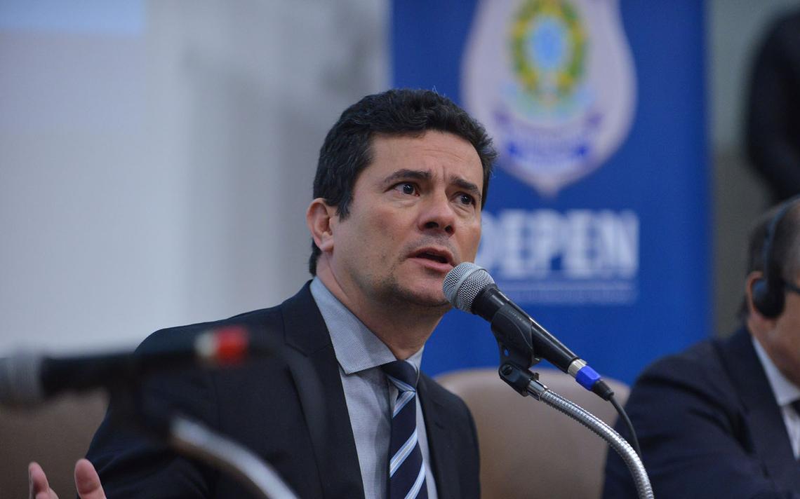 Sentado à mesa e dentro de auditório, Sergio Moro gesticula e fala ao microfone. Atrás, cartaz com brasão da República e os dizeres