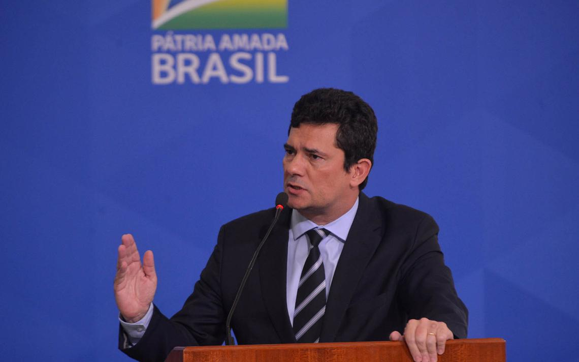 Em púlpito, Moro fala ao microfone e gesticula com a mão. Atrás, painel com o logotipo do governo Bolsonaro e o slogan