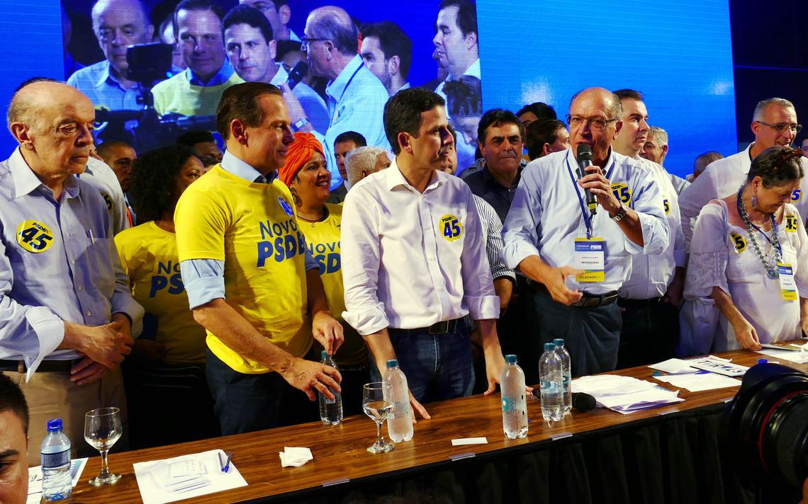 Alckmin fala ao microfone. Ao lado dele, Bruno Araújo, Doria e Serra o observam.