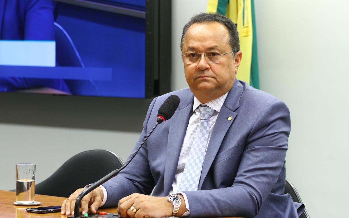 Silas Câmara sentado em comissão. À frente, um microfone. Atrás, uma bandeira verde-amarela e a televisão que transmite a sessão.